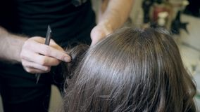 Zbliżenie fryzjera mężczyzna robi fryzurze dla młodej kobiety w piękno salonie zdjęcie wideo