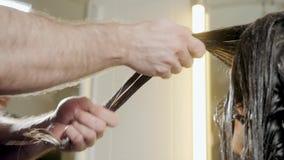 Zbliżenie fryzjera mężczyzna robi fryzurze dla młodej kobiety w piękno salonie zbiory