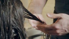Zbliżenie fryzjera mężczyzna robi fryzurze dla młodej kobiety w piękno salonie zbiory wideo