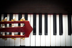 Zbliżenie głowa gitara na fortepianowej klawiaturze Fotografia Stock