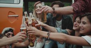 Zbliżenie grupa duzi przyjaciele pije piwo, otuchy z each inny obok retro pomarańczowego samochodu dostawczego, bardzo eleganccy  zbiory wideo
