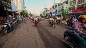 Zbliżenie hulajnoga przejażdżka wzdłuż ruchliwej ulicy domami w ranku zdjęcie wideo