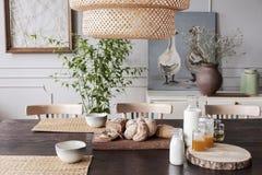 Zbliżenie jadalnia stół z słomianymi kabotażowami chleb, mleko i dżem maluje z dwa ślicznymi kaczkami na półce za nim, zdjęcie royalty free