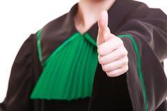 Zbliżenie jest ubranym klasyczną połysk togę pokazuje kciuk up prawnika adwokat Fotografia Stock