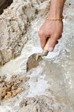 Zbliżenie kamieniarza ręka rozprzestrzenia świeżą betonową mieszankę z kielnią Obrazy Royalty Free