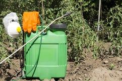 Zbliżenie kiści pompa, ochronne rękawiczki, respirator, nakrętka w ogródzie Przygotowanie dla rozpylać tomatoe rośliny obraz stock