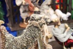 Zbliżenie kierownicza wielbłądzia figurka z zamazanymi postaciami od narodzenie jezusa sceny w tle fotografia stock