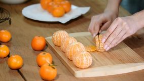 Zbliżenie kobiet ręki pokrajać wapna tangerine zbiory