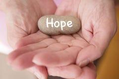 Zbliżenie kobiet ręki trzyma kamiennymi z słowo nadzieją Fotografia Stock