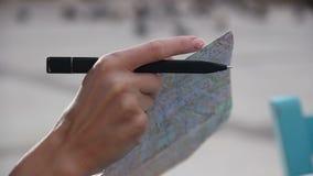 Zbliżenie kobiet ręki trzyma miasto mapę, zwiedzająca wycieczka turysyczna, sprawdza kierunek zdjęcie wideo