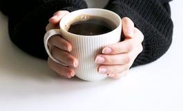 Zbliżenie kobiet ręki w czarnym trykotowym pulowerze trzyma filiżanka kawy Pusta kubka mockup scena Zima projekt femininely fotografia royalty free