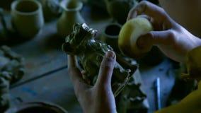 Zbliżenie kobieta czyści glinianą rzeźbę z specjalną gąbką zbiory