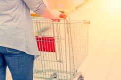 Zbliżenie kobieta plecy z wózek na zakupy w supermarkecie i ręka bagaże tła koncepcję czworonożne zakupy białą kobietę stonowany Zdjęcie Stock