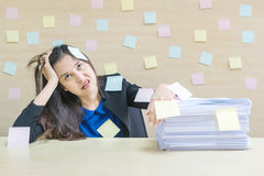 Zbliżenie kobieta pracująca zanudza od stosu ciężkiej pracy i pracy papier przed ona w pracy pojęciu na zamazanym drewnianym biur Zdjęcia Royalty Free
