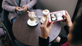 Zbliżenie kobieta wręcza fotografować filiżankę używać smartphone w ulicznej kawiarni podczas gdy siedzący outdoors Obrazy Royalty Free