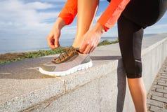 Zbliżenie kobieta wręcza wiązać działających butów koronki Zdjęcia Royalty Free