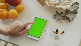 Zbliżenie kobiety ` s ręka wyszukuje smartphone z zieleń ekranem na kuchennym stole w domu zdjęcie wideo