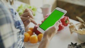 Zbliżenie kobiety ` s ręka wyszukuje smartphone z zieleń ekranem na kuchni w domu zbiory