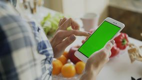 Zbliżenie kobiety ` s ręka wyszukuje smartphone z zieleń ekranem na kuchni w domu zdjęcie royalty free