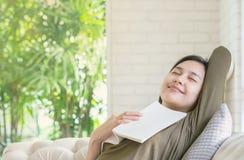Zbliżenie kobiety sen przy kanapą z książką w jej ręce w szczęśliwej twarzy emoci przy żywym pokojem textured tło Obrazy Royalty Free