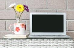 Zbliżenie komputer na zamazanym drewnie wyplata stołowego i brown ściana z cegieł tekstury tło, piękny miejsca pracy wnętrze domo Fotografia Royalty Free