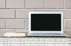 Zbliżenie komputer na zamazanym drewnie wyplata stołowego i brown ściana z cegieł tekstury tło, piękny miejsca pracy wnętrze domo Zdjęcie Stock
