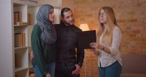 Zbliżenie krótkopęd ściska radośnie indoors młoda szczęśliwa muzułmańska para opowiada realter w niedawno kupującym mieszkaniu zbiory wideo