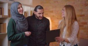 Zbliżenie krótkopęd ściska radośnie młoda szczęśliwa muzułmańska para opowiada realter pozycja w niedawno kupującym mieszkaniu zdjęcie wideo