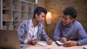 Zbliżenie krótkopęd śmia się amerykanin afrykańskiego pochodzenia i indyjscy męscy ucznie dyskutuje projekt na szczęśliwie wpólni zbiory wideo