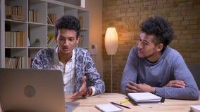 Zbliżenie krótkopęd amerykanin afrykańskiego pochodzenia i indyjscy męscy ucznie dyskutuje projekt wpólnie używa na brać i laptop zdjęcie wideo