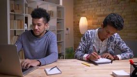 Zbliżenie krótkopęd amerykanin afrykańskiego pochodzenia i indyjscy męscy ucznie pracuje na projekcie wpólnie Jeden pisać na masz