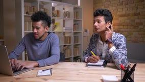 Zbliżenie krótkopęd amerykanin afrykańskiego pochodzenia i indyjscy męscy ucznie uczy się wpólnie Jeden pisać na maszynie na lapt zbiory