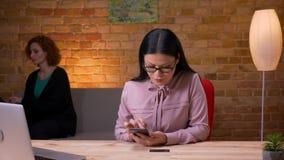Zbliżenie krótkopęd dorosły azjatykci bizneswoman robi zakupy online na telefonie przed laptopem indoors w biurze zdjęcie wideo