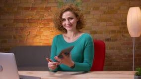 Zbliżenie krótkopęd dorosły bizneswoman używa pastylkę przed laptopem i pokazywać błękitnego ekran kamera indoors zbiory wideo