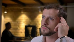 Zbliżenie krótkopęd dorosły caucasian męski pracownik jest rozważny i szuka rozwiązanie dla zadania indoors w biurze fotografia royalty free