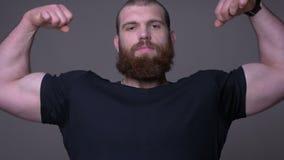 Zbliżenie krótkopęd dorosły przystojny caucasian mężczyzna patrzeje kamerę z tłem z brodą pokazuje jego silnych mięśnie zdjęcie wideo