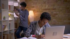 Zbliżenie krótkopęd dwa kulturowo różnorodnego ucznia uczy się w szkolnej bibliotece indoors Indiański męski studiowanie online d