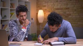 Zbliżenie krótkopęd indyjski studencki nauczanie i pomagać jego amerykanin afrykańskiego pochodzenia przyjaciela z szkolnym proje zdjęcie wideo