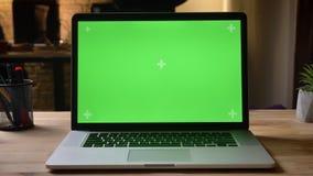 Zbliżenie krótkopÄ™d kamerÄ… poruszajÄ…cÄ… laptop z zielonym chroma klucza ekranem z reklamÄ… na nim na stole wokoÅ'o zdjęcie wideo