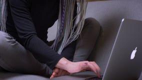 Zbliżenie krótkopęd kamery chodzeniem od młodej atrakcyjnej caucasian modniś kobiety pisać na maszynie na z dreadlocks ręki zbiory wideo