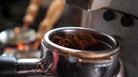 Zbliżenie krótkopęd kawowe fasole świeżo grinded w kawowej kontaminacji maszynie indoors w kawiarni zbiory wideo
