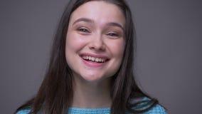 Zbliżenie krótkopęd młoda ładna brunetki kobieta z stokrotka kolczykami uśmiechniętymi i śmiają się patrzejący kamerę z tłem zbiory