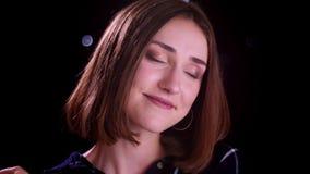 Zbliżenie krótkopęd młoda ładna krótka z włosami żeńska uśmiechnięta i patrzeje kamera z czułością z bokeh zaświeca na zbiory wideo