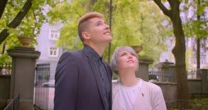 Zbliżenie krótkopęd młoda ładna modniś para opowiada radośnie ściskać kamerę jest szczęśliwy w parku patrzeć i zbiory wideo