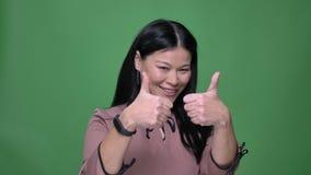Zbliżenie krótkopęd młoda atrakcyjna azjatykcia kobieta uśmiecha się kciuk w górę pokazywać zgodę z i gestykuluje z czarni włosy zbiory wideo