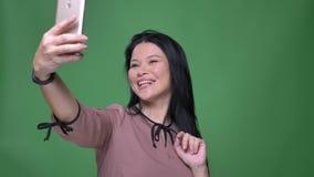 Zbliżenie krótkopęd młoda atrakcyjna azjatykcia kobieta z czarni włosy bierze selfies na telefonie i pozuje przed zbiory