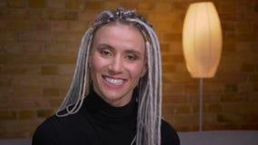 Zbliżenie krótkopęd młoda atrakcyjna caucasian kobieta patrzeje kamerę i ono uśmiecha się szczęśliwie indoors z blondynek dreadlo zdjęcie wideo