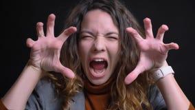 Zbliżenie krótkopęd młoda atrakcyjna caucasian kobieta robi śmiesznemu wyrazowi twarzy i ryczy w przodzie od kamerę fotografia stock