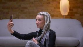 Zbliżenie krótkopęd młoda atrakcyjna caucasian kobieta z blondynek dreadlocks bierze selfies na telefonie pozuje przed zbiory
