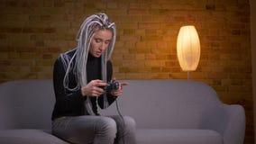 Zbliżenie krótkopęd młoda atrakcyjna caucasian modniś kobieta bawić się gra wideo na TV i dostaje szczęśliwego obsiadanie na zbiory wideo